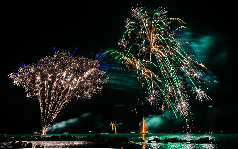 Gold and green fireworks in Sardinia during a corporate event on the shore.